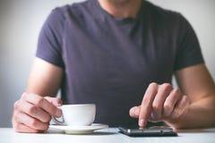 Trinkender Morgenkaffee des jungen Mannes und halten Handy Süßes Hörnchen und ein Tasse Kaffee im Hintergrund Bemannen Sie das Ha Lizenzfreie Stockfotos