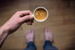 Trinkender Morgenkaffee des jungen Mannes und halten Handy Süßes Hörnchen und ein Tasse Kaffee im Hintergrund Bemannen Sie das Ha Lizenzfreie Stockfotografie