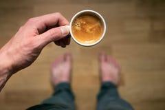 Trinkender Morgenkaffee des jungen Mannes und halten Handy Süßes Hörnchen und ein Tasse Kaffee im Hintergrund Bemannen Sie das Ha Stockbilder