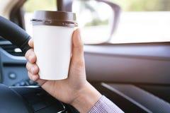 Trinkender Papierschalenkaffee von hei?em in der Hand beim Fahren in ein Auto stockbilder