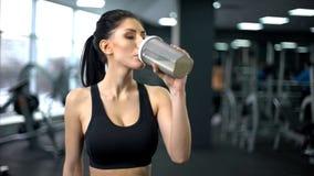 Trinkender Proteindrink der sportlichen Frau nach Training, Muskelgewinnnahrung, Gesundheit stockfotografie