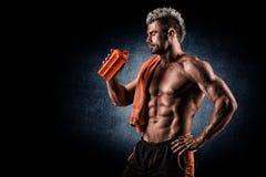Trinkender Proteindrink des jungen erwachsenen Mannes in der Turnhalle Schwarzer Hintergrund Stockfotos