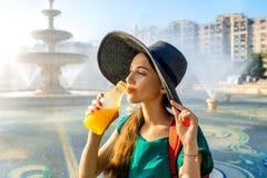 Trinkender Saft der Frau nahe dem Brunnen Stockfotografie