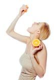 Trinkender Saft der Frau von einer orange Frucht Lizenzfreie Stockfotos