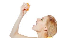 Trinkender Saft der Frau von einer orange Frucht Stockfoto