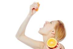 Trinkender Saft der Frau von einer orange Frucht Stockfotos