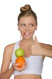 Trinkender Saft der glücklichen Frau vom Apfel, orange Stockfotografie