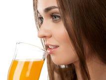 Trinkender Saft der jungen Frau, auf dem weißen Hintergrund Lizenzfreies Stockfoto