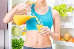 Trinkender Saft der jungen Frau und nahe dem Kühlschrank von Biokost voll staing Lizenzfreie Stockfotos