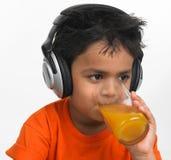 Trinkender Saft des Jungen mit Kopfhörer Lizenzfreies Stockbild