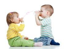 Trinkender Saft des Jungen und des Mädchens vom Glas Stockbilder