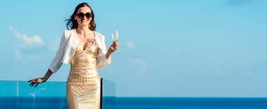 Trinkender Sekt der Frau, der über Ozean schaut Lizenzfreie Stockbilder