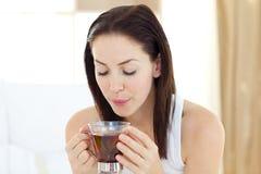 Trinkender Tee der begeisterten Frau Stockfotografie