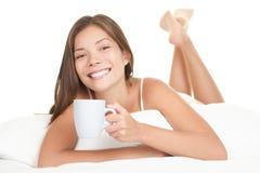 Trinkender Tee der Bettfrau Stockfoto
