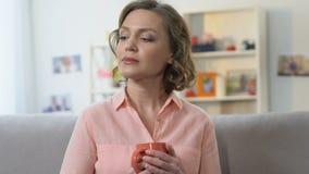 Trinkender Tee der einsamen traurigen Frau auf dem Sofa, Entscheidung von Lebenschwierigkeiten erwägend stock video