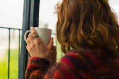 Trinkender Tee der Frau durch Thfenster Stockfoto