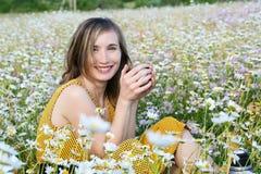 Trinkender Tee der Frau von einer Thermosflasche Stockfotos