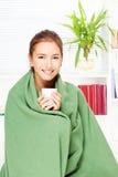 Trinkender Tee der Frau zu Hause abgedeckt mit Decke Lizenzfreie Stockfotos