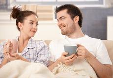Trinkender Tee der glücklichen Paare beim Bettlächeln Stockfotografie