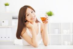 Trinkender Tee der jungen asiatischen Frau Stockfotos