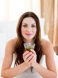 Trinkender Tee der jungen Brunettefrau, der auf Bett sitzt Stockbild