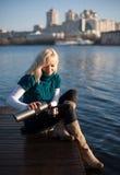 Trinkender Tee der jungen Frau auf Pier Lizenzfreie Stockbilder