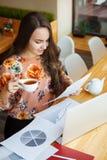 Trinkender Tee der jungen Frau, Papiere lesend stockfotografie