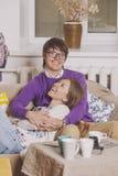 Trinkender Tee der jungen Paare in der Diskussion über Ideen Stockfotografie