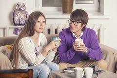 Trinkender Tee der jungen Paare in der Diskussion über Ideen Stockfotos