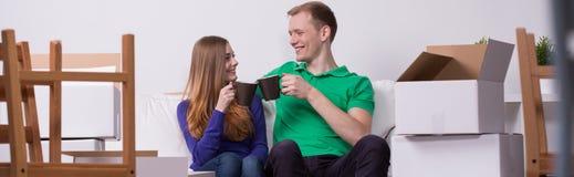 Trinkender Tee der Paare im neuen Haus Stockbild