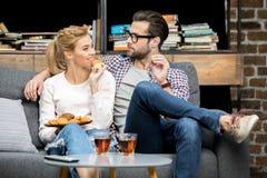 Trinkender Tee der Paare mit Keksen Stockbilder