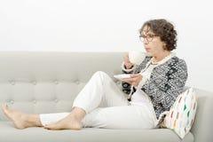 Trinkender Tee der reifen Frau auf dem Sofa Lizenzfreie Stockfotos