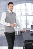 Trinkender Tee des jungen Geschäftsmannes beim Bürolächeln lizenzfreies stockbild
