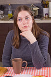 Trinkender Tee des jungen Mädchens an der Küche Stockfotos