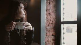 Trinkender Tee des jungen Mädchens von einem Becher und das Fenster heraus von schauen, das im modernen Dachboden speist 4k sitzt Stockfoto