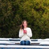 Trinkender Tee des jungen schönen Mädchens in einem kühlen Winterpark Stockfotos
