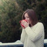 Trinkender Tee des jungen schönen Mädchens in einem kühlen Winterpark Lizenzfreie Stockfotografie