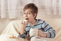 Trinkender Tee des Jungen und essen Kekse Stockfoto