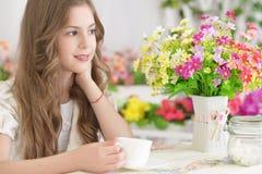 Trinkender Tee des kleinen Mädchens Stockfoto
