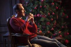 Trinkender Tee des männlichen Abends am Weihnachtsbaum Lizenzfreie Stockfotos