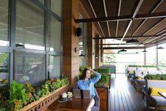 Trinkender Tee des reizend Mädchens am Restaurant stockbild