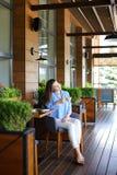 Trinkender Tee des reizend Mädchens am Restaurant stockfotos