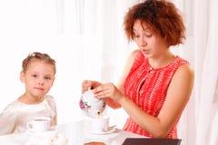 Trinkender Tee des schönen Kindes und des jungen Mädchens lizenzfreie stockfotos