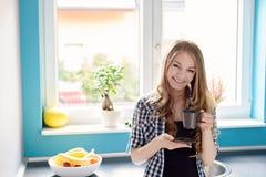 Trinkender Tee oder Kaffee der jungen blonden Frau von der braunen Schale Stockbilder