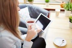 Trinkender Tee und Anwendung der Tablette Stockfoto