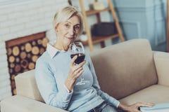Trinkender Wein der entspannten Blondine stockfotografie