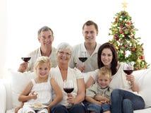 Trinkender Wein der Familie und essen Bonbons Stockfotografie