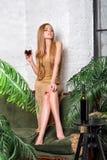 Trinkender Wein der Frau Schöne junge Blondine im langen goldenen Abendkleid mit Glas Rotwein im Luxusdachboden Stockfoto