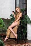 Trinkender Wein der Frau Schöne junge Blondine im langen goldenen Abendkleid mit Glas Rotwein im Luxusdachboden Stockfotos
