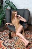 Trinkender Wein der Frau Schöne junge Blondine im langen goldenen Abendkleid mit Glas Rotwein im Luxusdachboden Lizenzfreie Stockfotografie